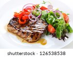 Grilled steak meat with salad from baked pepper on white plate. - stock photo