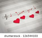 """Small photo of Words """"I love you !"""" in shape of music notes in the music note book with red hearts"""