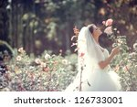 Beautiful Bride smell the roses. Wedding theme with flowers - stock photo