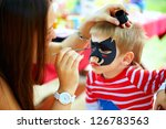 Woman Painting Face Of Kid...