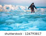Man walking on icy beach along the Baltic sea - stock photo
