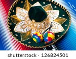 Mexican sombrero with maracas on a colorful striped poncho - stock photo