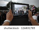 BANGKOK - NOV 24: A protesters uses a tablet computer to photograph an anti-government rally organised by the nationalist Pitak Siam group on Nov 24, 2012 in Bangkok, Thailand. - stock photo