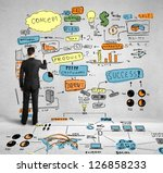businessman drawing colorized global concept on wall - stock photo