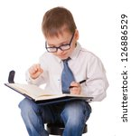 Small clever boy make notes about his plans in organizer notebook. Isolated on white background. - stock photo