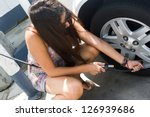 Young woman adds air to her car tire. - stock photo