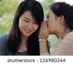 A girl whispering something to her friend. - stock photo