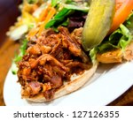 Delicious pub style pulled pork sandwich with pickle and salad on the side - stock photo