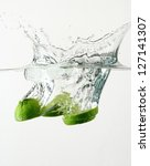 Fresh lime and ice cube splash - stock photo