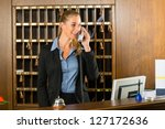 Reception of hotel, desk clerk, woman taking a call and smiling - stock photo