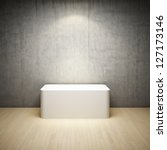 Empty white stand in interior room with concrete wall and spotlight - stock photo
