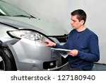 Insurance expert examining car damage. - stock photo