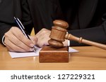 Referee hammer and a man in judicial robes - stock photo