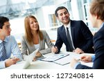 Image of business partners laughing during interaction at meeting - stock photo