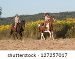 Two cowgirls riding a horse - stock photo