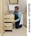 Carpenter installing wardrobe drawers in walk-in closet - stock photo
