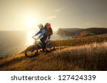 Young male traveler riding a mountain bike on a sunset - stock photo