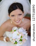 happy smiling bride with bouquet of flowers - stock photo