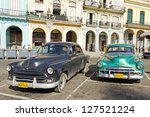 HAVANA-SEP 7: Old Plymouths parked front of the Capitol on Sep 7, 2011 in Havana. Before a new law issued on October 2011, cubans could only trade vintage cars that were on the road before 1959. - stock photo