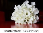 Calla Lily bridal bouquet with reflection on the red surface - stock photo