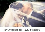 wedding couple kissing covered... | Shutterstock . vector #127598093