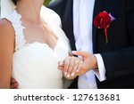 Bride and groom holding hands and showing the engagement ring - stock photo