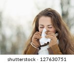 Woman blowing nose in winter outdoors - stock photo