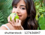Closeup potrait of young woman holding a green apple - stock photo
