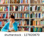 Portrait of clever student with open book reading it in college library - stock photo