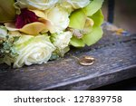 Wedding rings and white roses wedding bouquet - stock photo