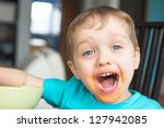 Boy with dirty face with spaghetti sauce on face - stock photo