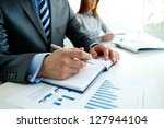 Image of male hand with pen over page of notebook at seminar - stock photo