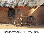 Mud huts and bike in a traditional African village - stock photo