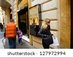 ROME - MARCH 13:  Luxury shopping along Via Condotti in Rome, Italy, on March 13, 2005. Shoppers pass a Gucci shop. - stock photo