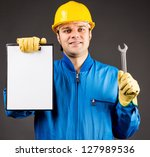 Portrait of a young worker holding a clipboard and a wrench on grey - stock photo