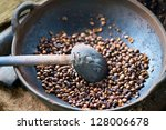 Traditional coffee beans roasting in metal basin with spoon, shallow depth of field - stock photo