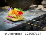 Traditional balinese offerings to gods in Bali with flowers and aromatic sticks - stock photo