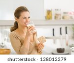 Young woman eating crisp bread with milk and looking on copy space - stock photo