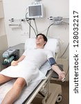 Male patient on hospital bed - stock photo