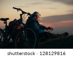 cyclist tourist guy sat down to rest at night with the tablet - stock photo