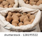 Bags with potatoes isolated on white background - stock photo