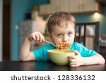 3 year old boy while eating spaghetti - stock photo