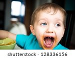 3 year old boy cries while eating dinner - stock photo