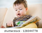 Cute little boy reading book on sofa - stock photo