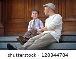 Happy father and son having rest outdoors in city - stock photo