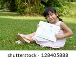 Little child shows drawing of her family member - stock photo