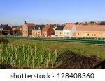 Brand new houses by an embankment with trees planted for noise reduction - stock photo