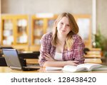 female student with laptop working in library. looking at camera - stock photo