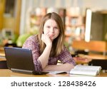 female student with laptop and books working in a high school library - stock photo