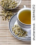 Dried camomile flowers surrounding fresh up of camomile tea - stock photo